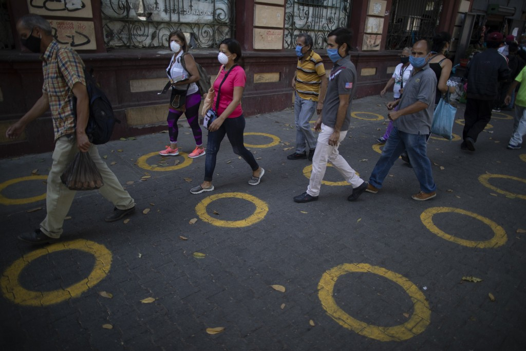 Yellow circles on a pavement serve as visual cues to help shoppers adhere to social distancing when lines form, to curb the spread of the new coronavi...