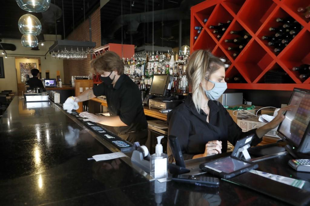 Deep Sushi restaurant employees Jordan Arrowood, left, cleans the bar top as Carrie Souza enters an order at the sushi restaurant in the Deep Ellum en...