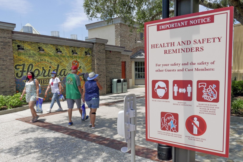 FILE - In this June 16, 2020, file photo, signs remind patrons to wear masks and other protocols because of the coronavirus pandemic as they stroll th...