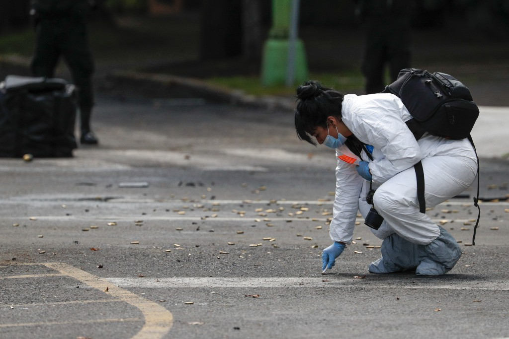 A forensic investigator collects cartridges at the scene where the Mexican capital's police chief was attacked by gunmen in Mexico City, Friday, June ...