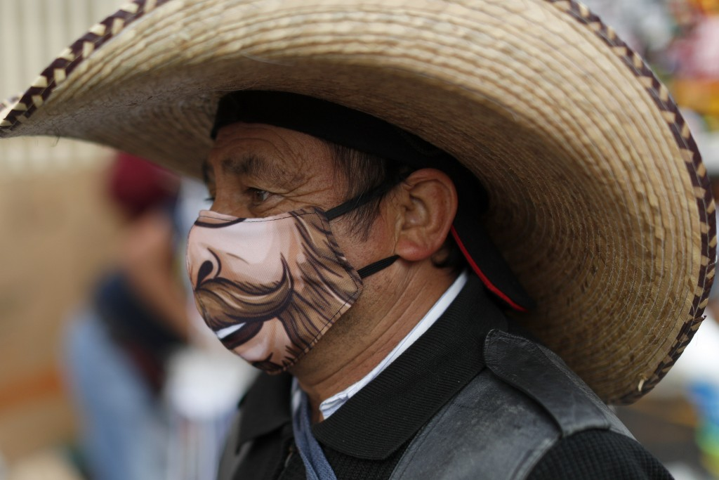 A man wearing a protective face mask walks amidst outdoor stalls at the Mercado Sonora, which reopened ten days ago with measures to reduce congestion...