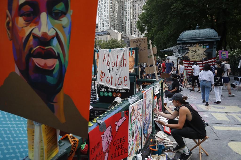 Protesters hang signs and artwork at a subway station entrance at an encampment outside City Hall, Friday, June 26, 2020, in New York. (AP Photo/John ...