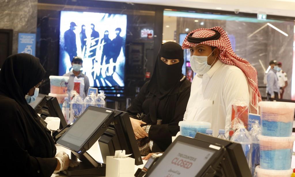 Saudi movie viewers wear face masks to help curb the spread of the coronavirus, as they buy refreshments at VOX Cinema hall in Jiddah, Saudi Arabia, F...