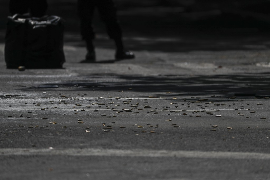 Cartridges carpet the pavement at the scene where the Mexican capital's police chief was attacked by gunmen in Mexico City, Friday, June 26, 2020. Hea...