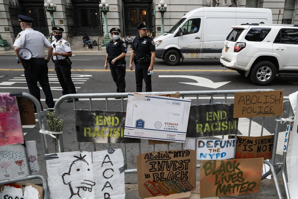 Police stand on the street beside a protest encampment surrounded by handmade signs and barricades outside City Hall, Friday, June 26, 2020, in New Yo...