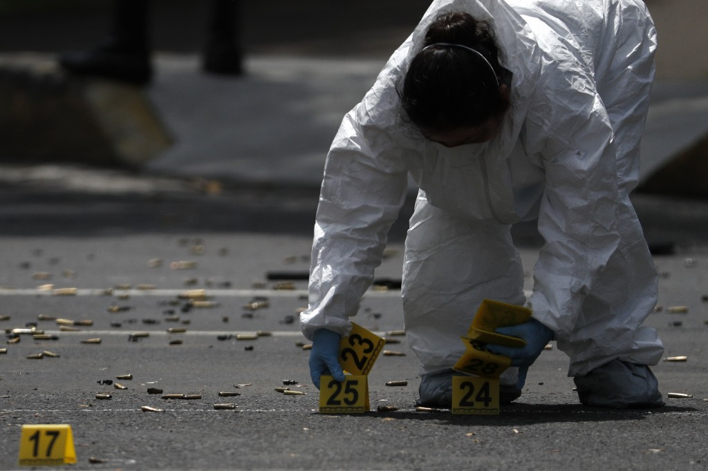 A forensic investigator tags cartridges at the scene where the Mexican capital's police chief was attacked by gunmen in Mexico City, Friday, June 26, ...