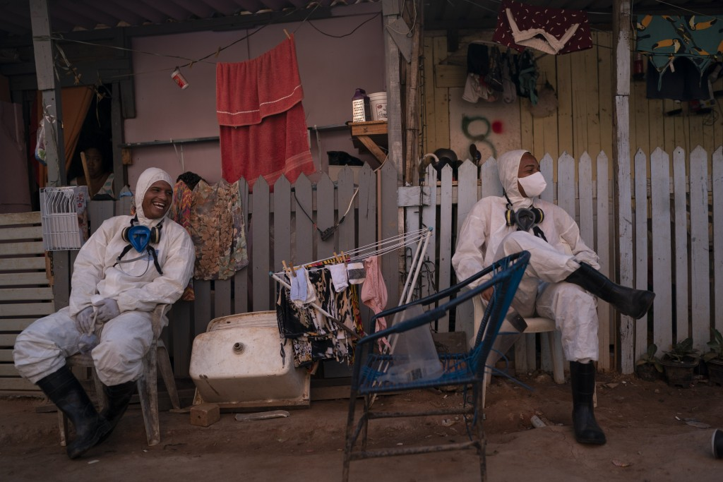 Welington Goncalves, right, sits next to his colleague as they wait to refill their tanks during a disinfection to help contain the spread of the new ...