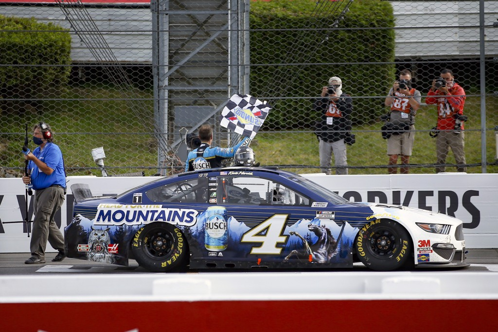 Kevin Harvick waves a checker flag for photographers after winning the NASCAR Cup Series auto race at Pocono Raceway, Saturday, June 27, 2020, in Long...