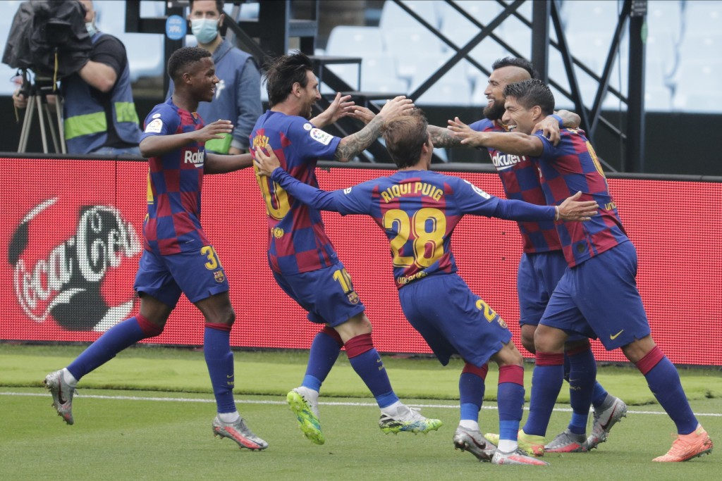 Barcelona's Luis Suarez, right, celebrates with teammates after scoring the opening goal during a Spanish La Liga soccer match between RC Celta and Ba...