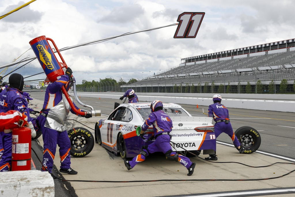 The crew refuels and changes tires for Denny Hamlin during a pit stop in the NASCAR Cup Series auto race at Pocono Raceway, Saturday, June 27, 2020, i...