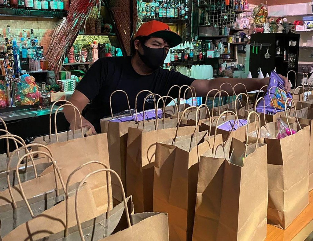 This photo provided by Lei Low Bar shows David Perez, organizing To-go orders at the Lei Low Bar in Houston on Thursday, June 25, 2020.  Businesses re...