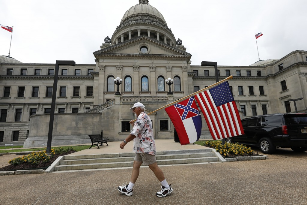 File-This June 27, 2020, file photo shows Don Hartness of Ellisville, Miss., walking around the Capitol carrying the current Mississippi state flag an...
