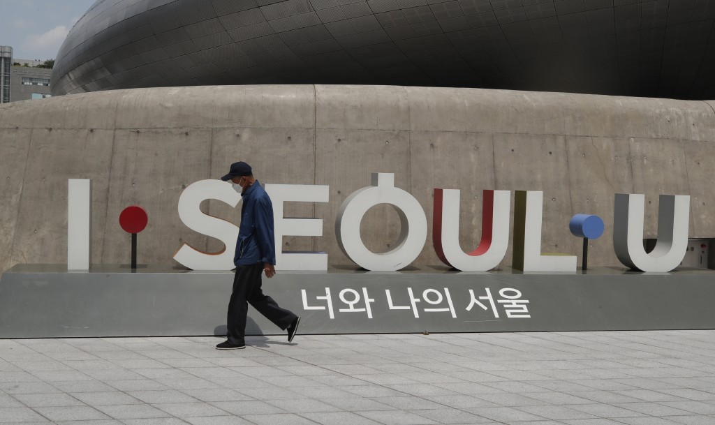 A man wearing a face mask walks in front of the display of South Korea's capital Seoul logo in Seoul, South Korea, Sunday, June 28, 2020. (AP Photo/Le...
