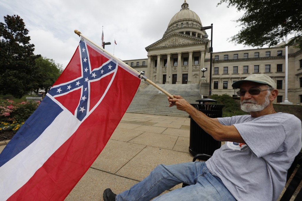 Larry Eubanks of Star waves the current Mississippi state flag as he sits before the front of the Capitol, Saturday, June 27, 2020, in Jackson, Miss. ...