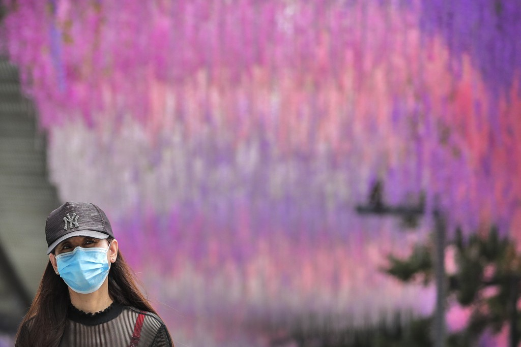 A woman wearing a protective face mask to help curb the spread of the coronavirus walks by a decoration outside a shopping mall in Beijing, Sunday, Ju...