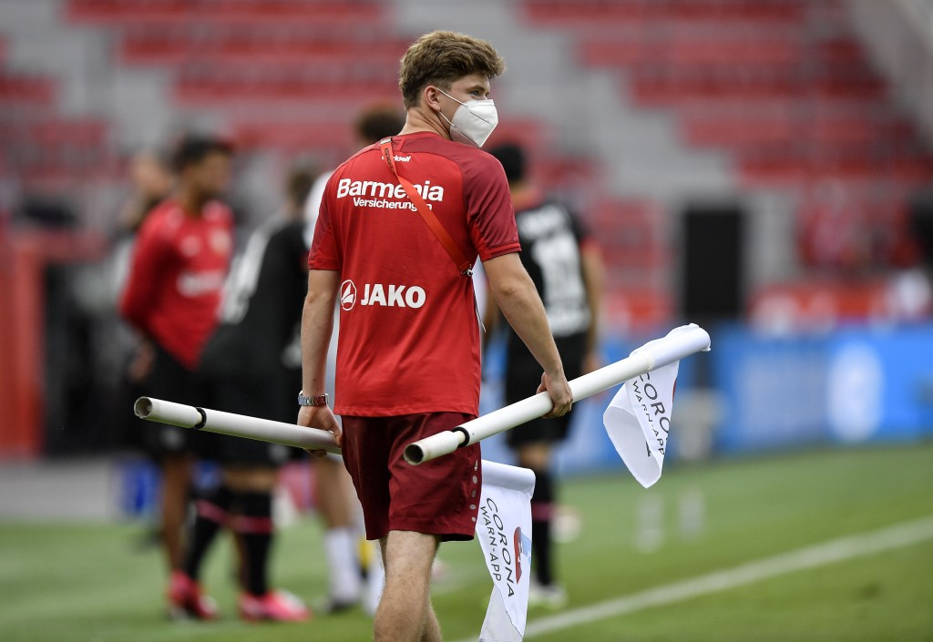 A ball boy carries the corner flags with a corona app commercial on it after the German Bundesliga soccer match between Bayer 04 Leverkusen and FSV Ma...