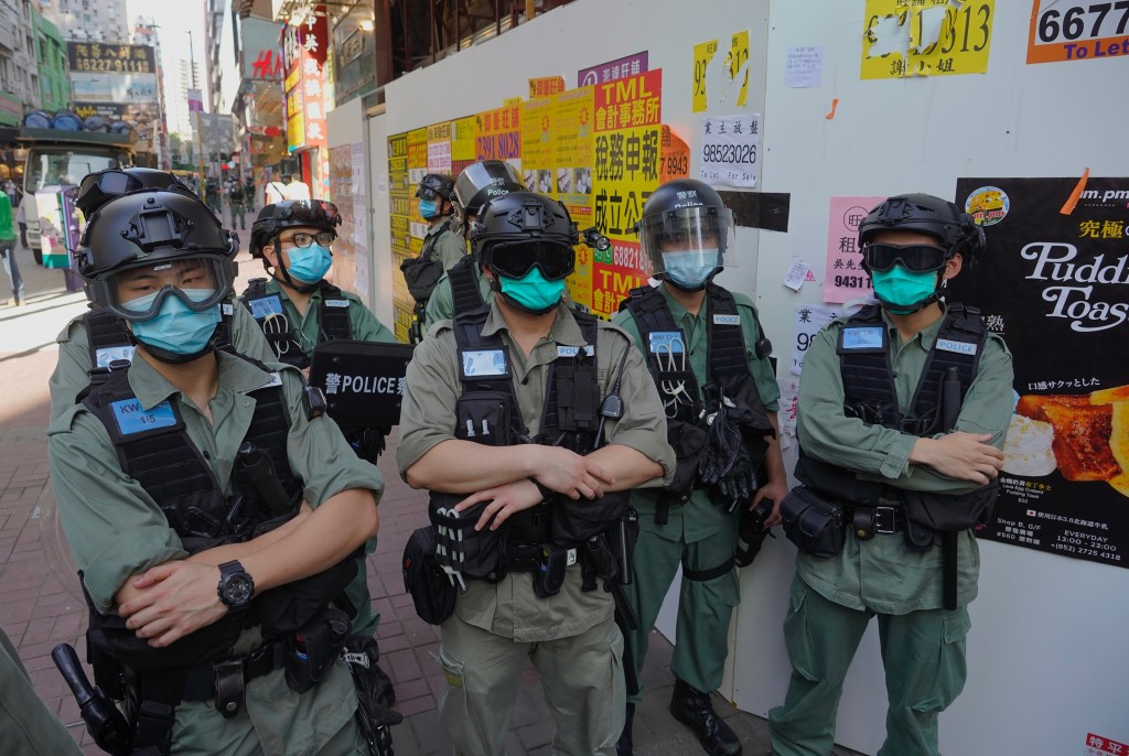 Police officers stand guard as people gather during a pro-democracy rally supporting human rights and to protest against Beijing's national security l...