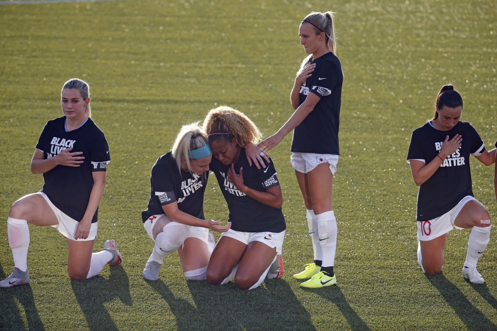 Chicago Red Stars' Julie Ertz, second from left, holds Casey Short, center, while other players for the team kneel during the national anthem before a...