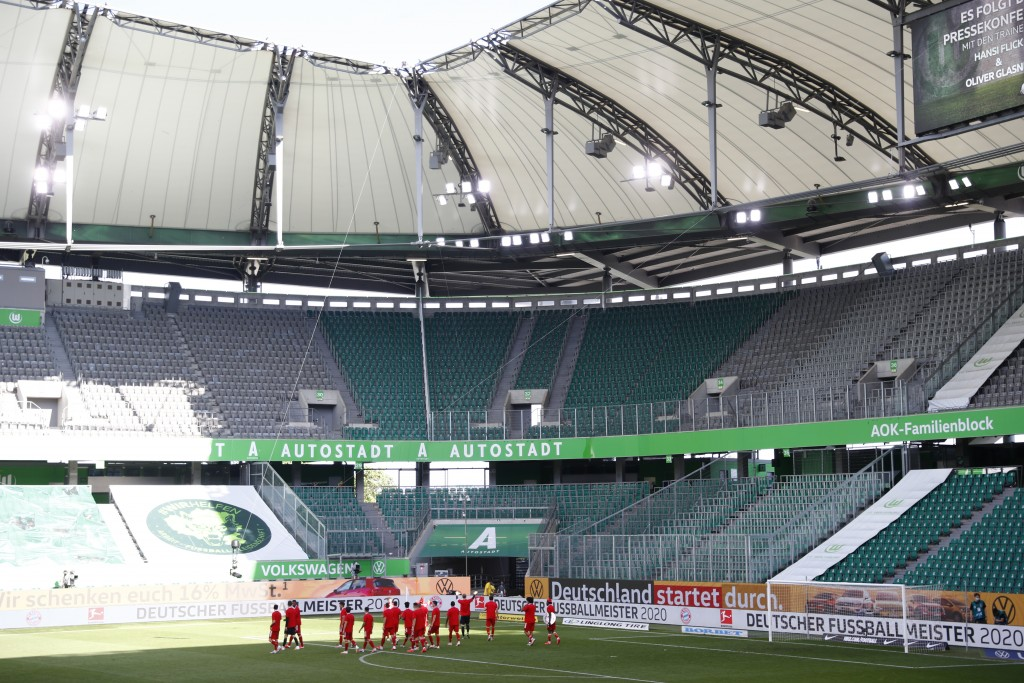 Munich's players celebrate in front of the empty stands after  the German Bundesliga soccer match between VfL Wolfsburg and FC Bayern Munich in Wolfsb...