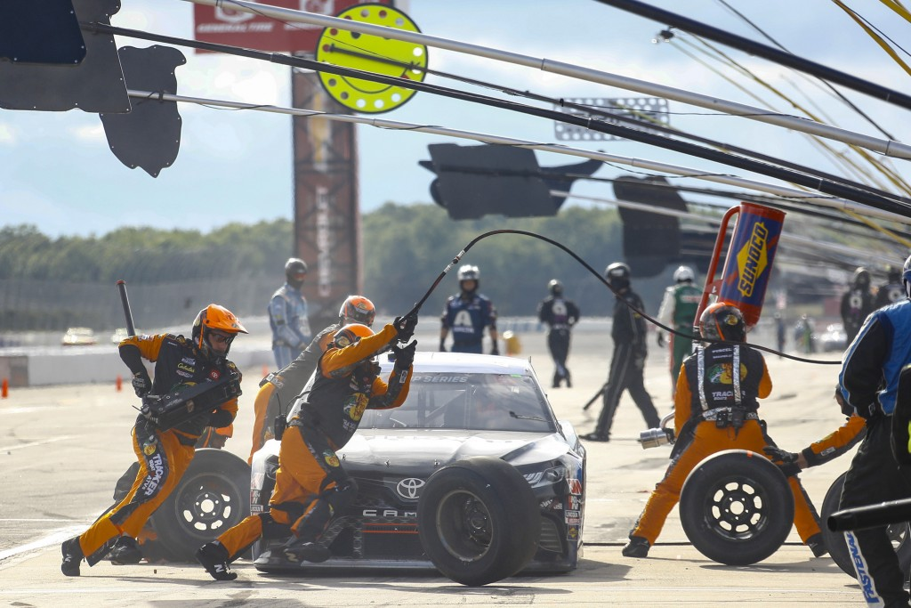 Crew members dash around the car of Martin Truex Jr. as they perform a pit stop during the NASCAR Cup Series auto race at Pocono Raceway, Saturday, Ju...
