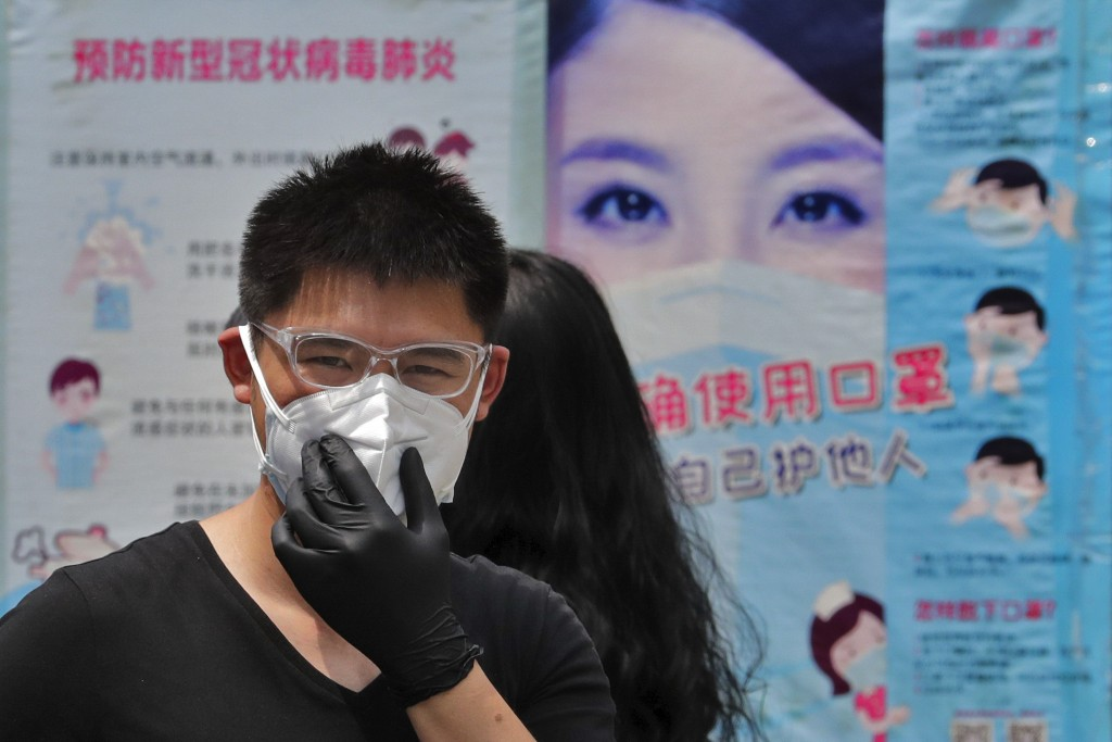 A man wearing groves adjusts his protective face mask as he walks by posters showing a proper way to wear a face mask to help curb the spread of the c...