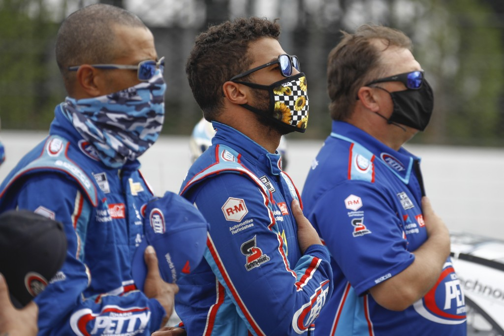 Bubba Wallace, center, stands with his crew during the playing of the national anthem before a scheduled NASCAR Cup Series auto race at Pocono Raceway...