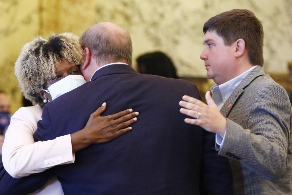 Sen. Sarita Simmons, D-Cleveland, left, hugs, Republican Sen. Brice Wiggins, of Pascagoula, center, and Jeremy England, of Vancleave, following the bo...