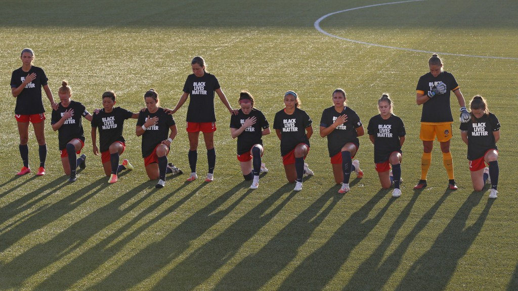 Players for the Washington Spirit kneel during the national anthem before an NWSL Challenge Cup soccer match against the Chicago Red Stars at Zions Ba...