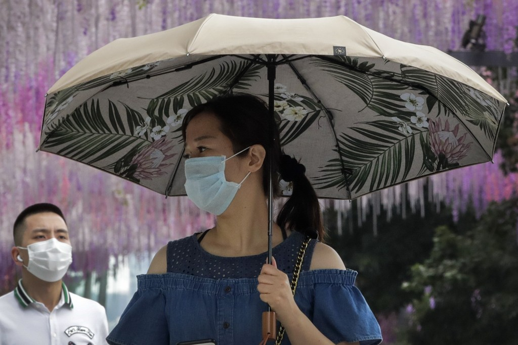 People wearing face masks to help curb the spread of the coronavirus walk by a decoration outside a shopping mall in Beijing, Sunday, June 28, 2020. C...