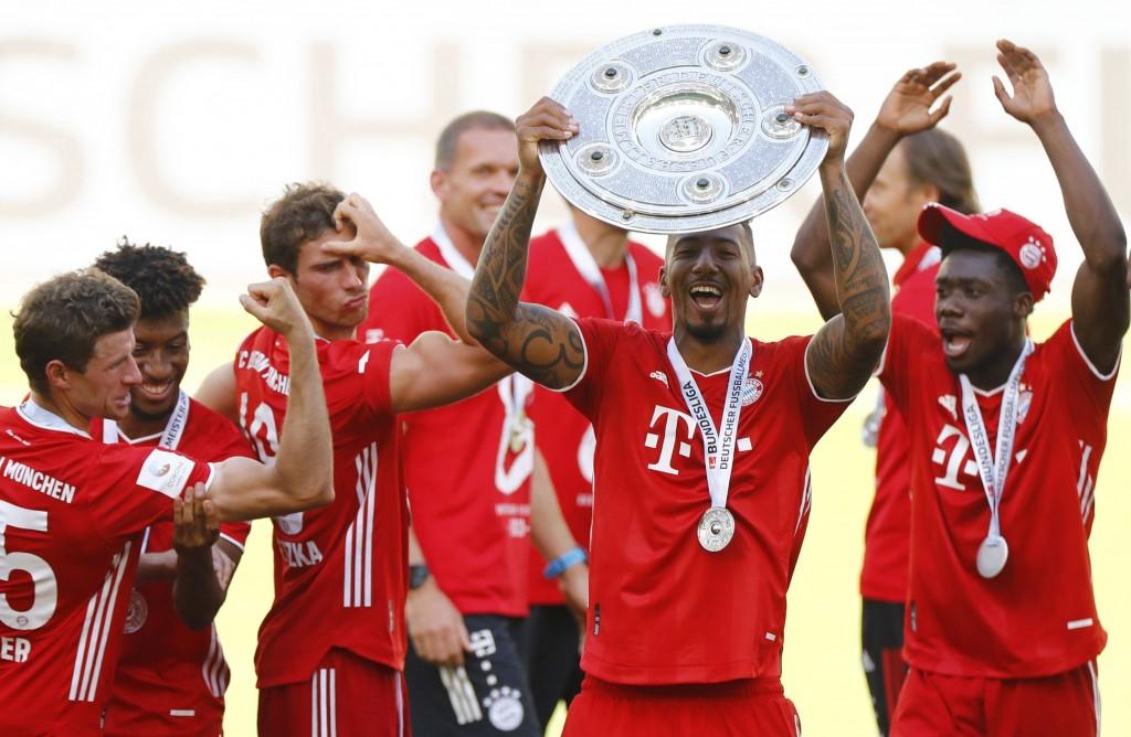 Munich's  Jerome Boateng lifts the trophy after  the German Bundesliga soccer match between VfL Wolfsburg and FC Bayern Munich in Wolfsburg, Germany, ...