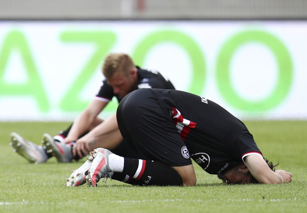 Players of Fortuna Düsseldorf sit and kneel on the pitch after a German Bundesliga soccer match between Union Berlin and Fortuna Duesseldorf in Berlin...