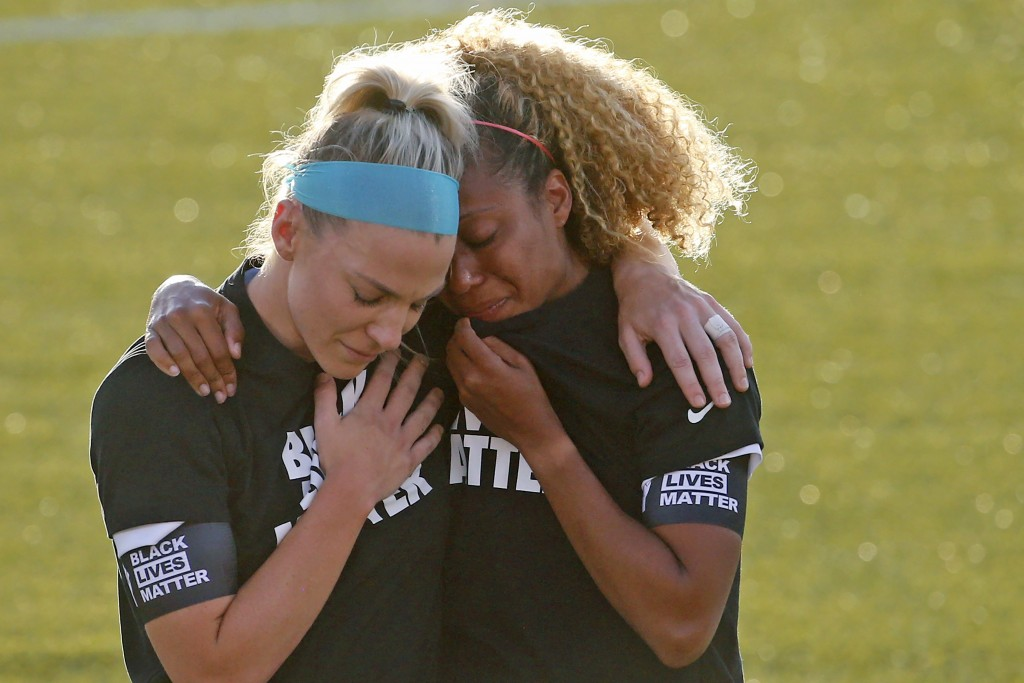 Chicago Red Stars' Julie Ertz, left, holds Casey Short after players for their team knelt during the national anthem before an NWSL Challenge Cup socc...