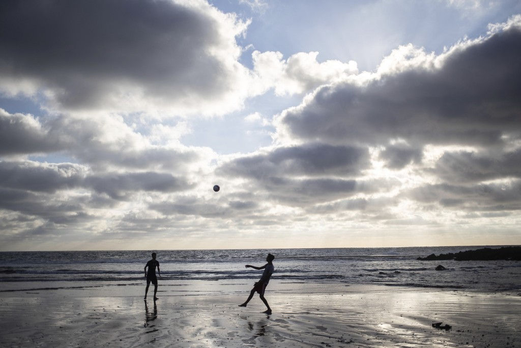 Boys play soccer as the sun sets on a reopened beach after lockdown measures were lifted in Rabat, Morocco, Friday, June 26, 2020. (AP Photo/Mosa'ab E...