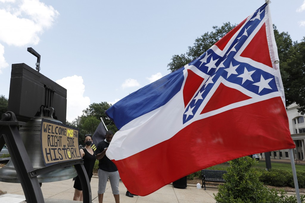 "A Mississippi state flag waves adjacent to a flag change supporter's sign that welcomes the state to ""the right side of history,"" outside the Capitol ..."