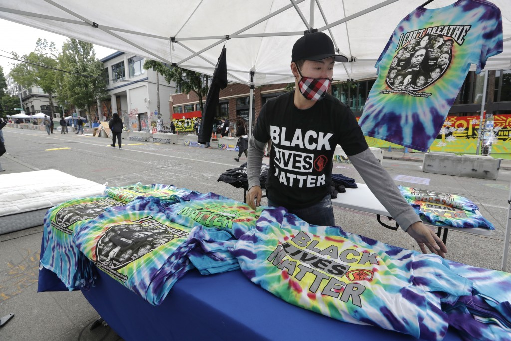 Tee shirt vendor Gavin Chung sets-up in view of a closed Seattle police precinct nearby Sunday, June 28, 2020, in Seattle, where streets are blocked o...