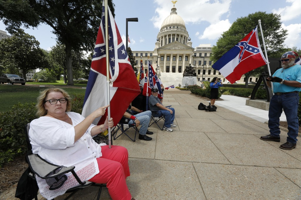 Tessa Collett of Petal, left, wants her vote to count as she supports the current flag as do other supporters standing outside the state Capitol in Ja...