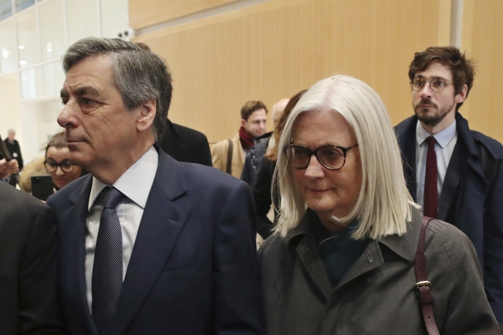 FILE - In this Feb. 26, 2020 file photo, France's former Prime Minister Francois Fillon, left, and his wife Penelope, arrive at the Paris courthouse, ...