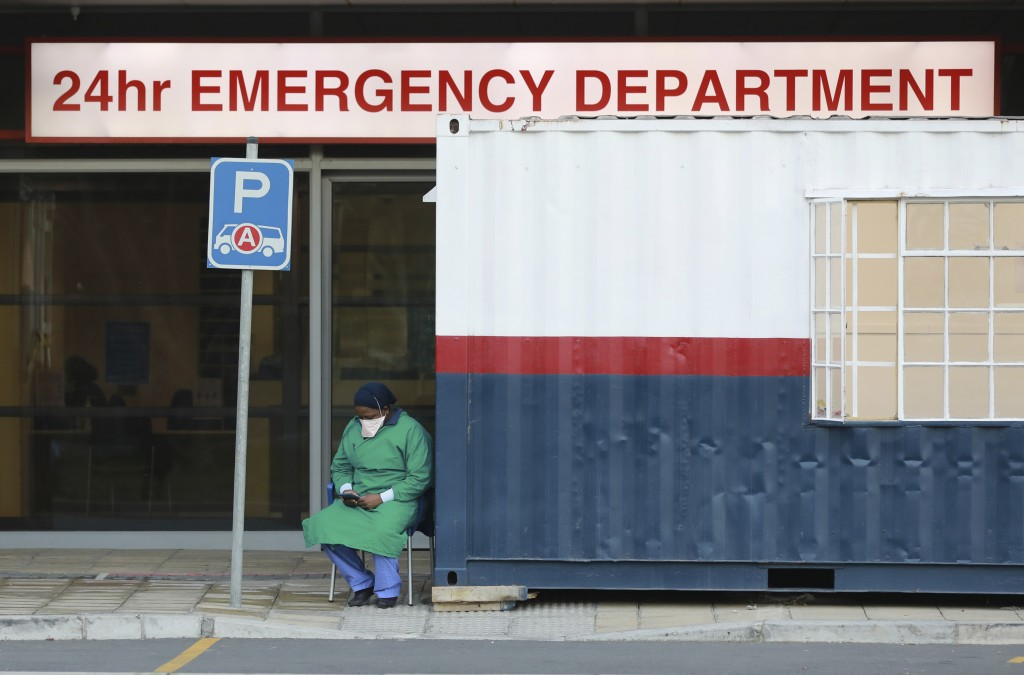 FILE — In this Wednesday June 17, 2020, file photo a health worker in personal protective gear takes a break at the Netcare Christiaan Barnard Memoria...
