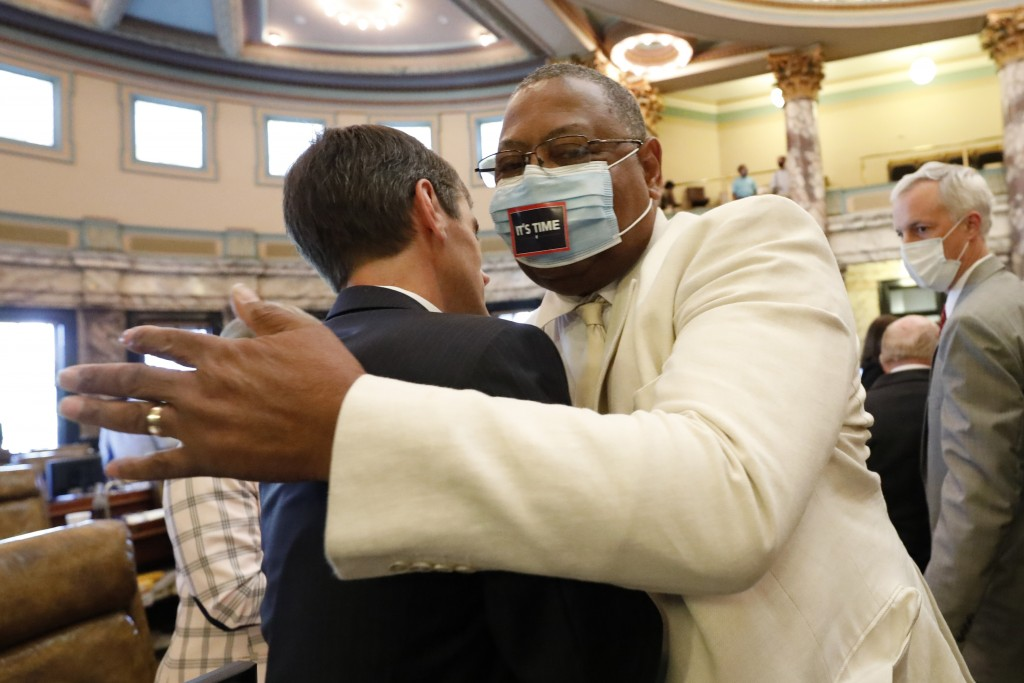 Sen. Briggs Hopson, left, R-Vicksburg, is hugged by Sen. Robert Jackson, D-Marks, after the Senate voted to change the state flag, Sunday, June 28, 20...