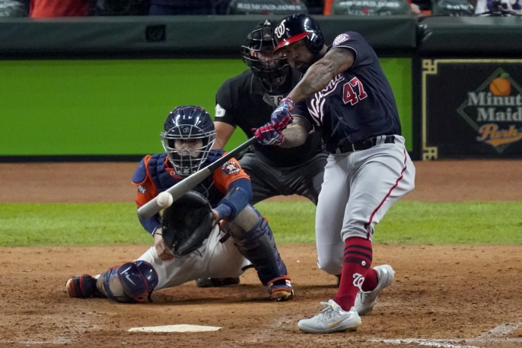 FILE - In this Oct. 30, 2019, file photo, Washington Nationals' Howie Kendrick hits a two-run home run against the Houston Astros during the seventh i...