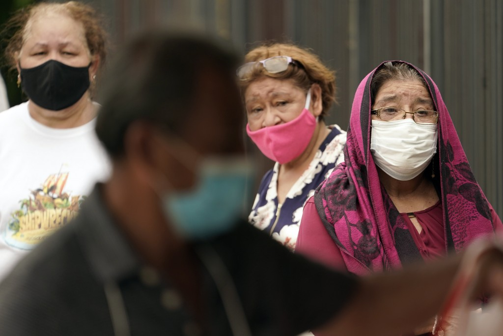 People wait in line at a free COVID-19 testing site provided by United Memorial Medical Center, Sunday, June 28, 2020, at the Mexican Consulate, in Ho...