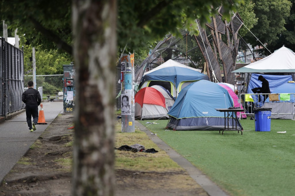 A jogger, left, runs past tents set-up on a play field in a city park Sunday, June 28, 2020, in Seattle, where several streets are blocked off in what...