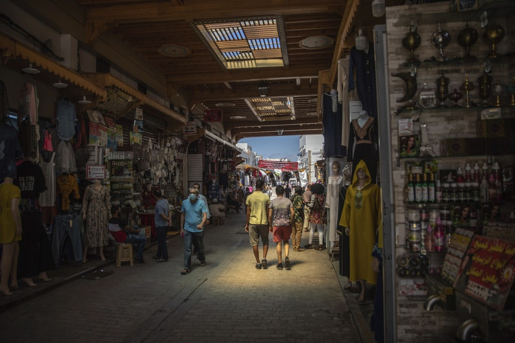 People walk past reopened shops in the Rabat Medina after lockdown measures were lifted in Rabat, Morocco, Friday, June 26, 2020. With the exception o...