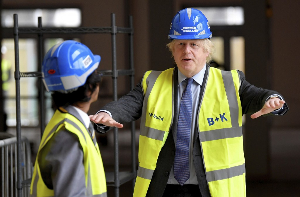 Britain's Prime Minister Boris Johnson talks with year 10 pupil Vedant Jitesh during a visit to the construction site of Ealing Fields High School in ...
