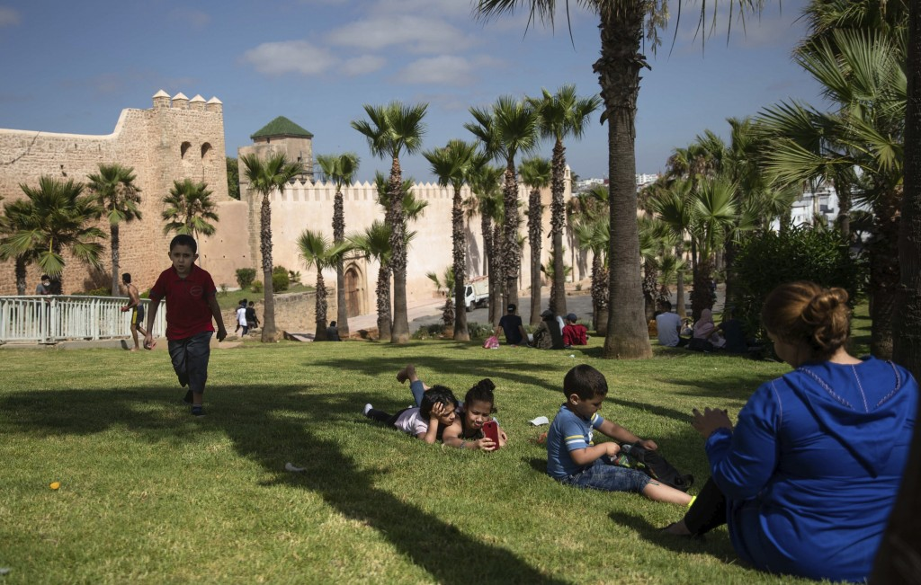 Families spend time at a reopened park after lockdown measures were lifted in Rabat, Morocco, Friday, June 26, 2020. In the capital Rabat, people welc...