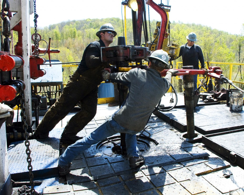 FILE - In this April 23, 2010, file photo, workers move a section of well casing into place at a Chesapeake Energy natural gas well site near Burlingt...