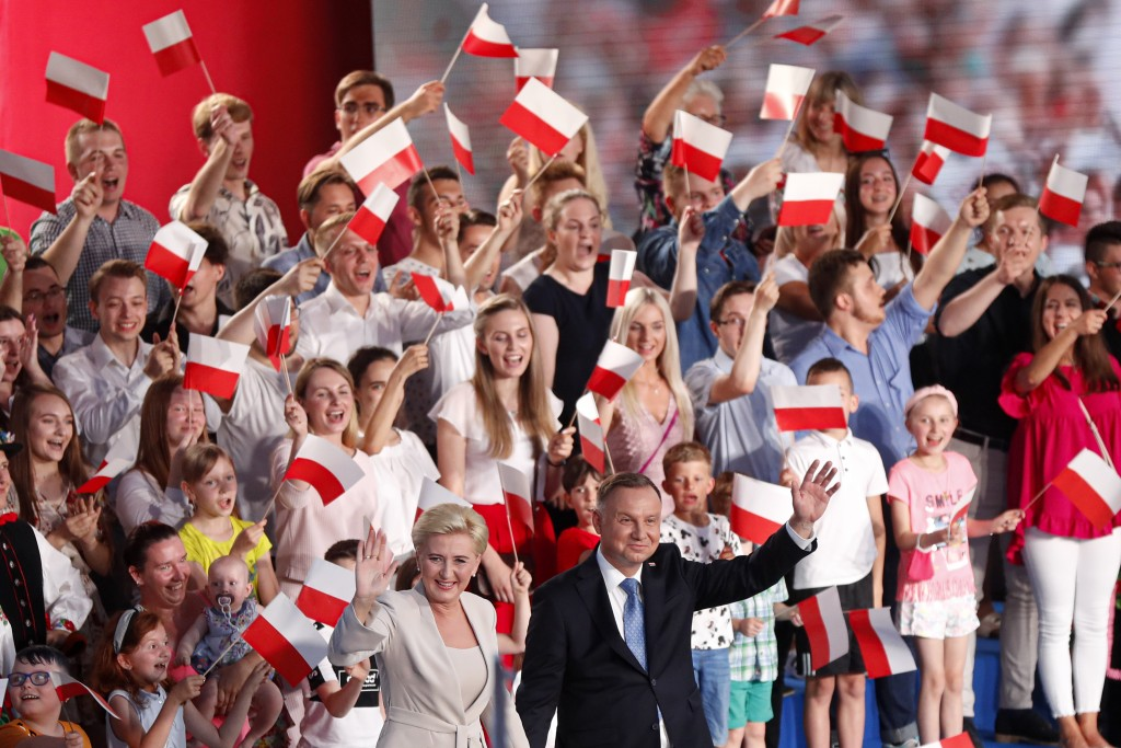 President Andrzej Duda and his wife Agata Kornhauser-Duda wave to supporters shortly after voting ended in the presidential election in Lowicz, Poland...