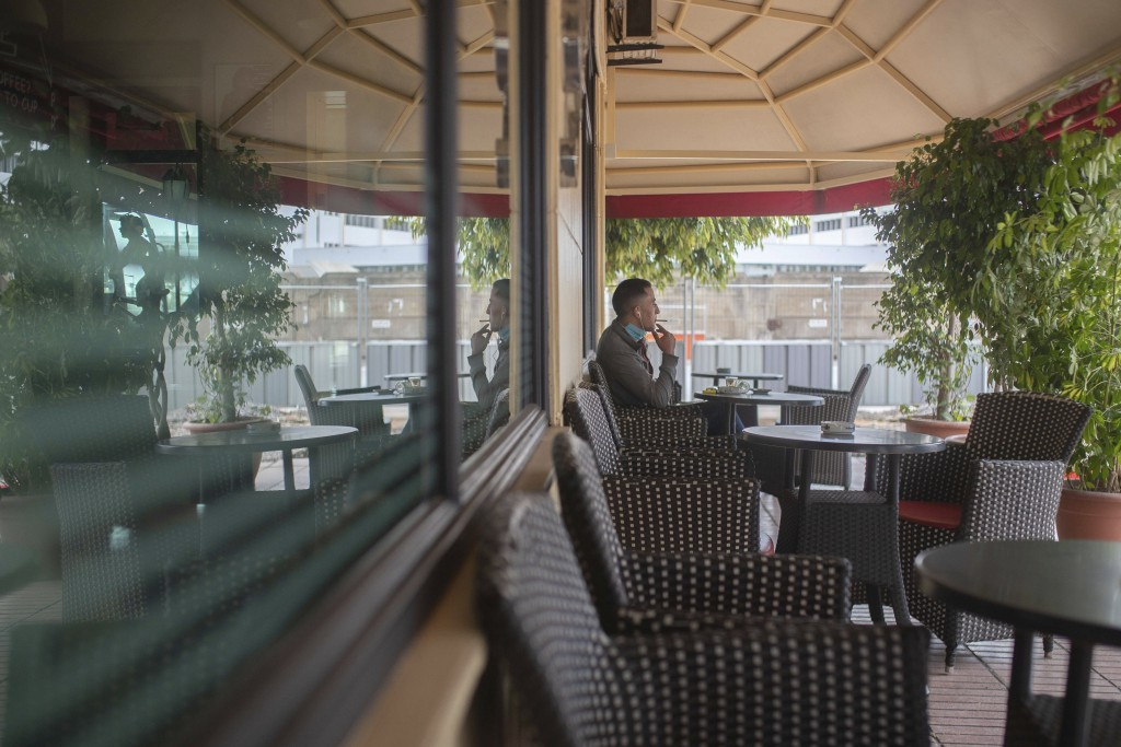 A man puts down his face mask to smoke a cigarette as he sits in a reopened coffeeshop after lockdown measures were lifted in Rabat, Morocco, Thursday...