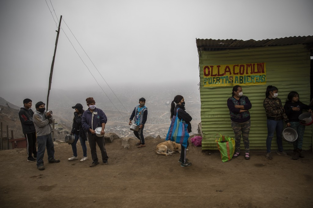 """Residents wait in line at a """"community pot,"""" in the Nueva Esperanza neighborhood of Lima, Peru, Wednesday June 17, 2020. For many residents the """"commu..."""