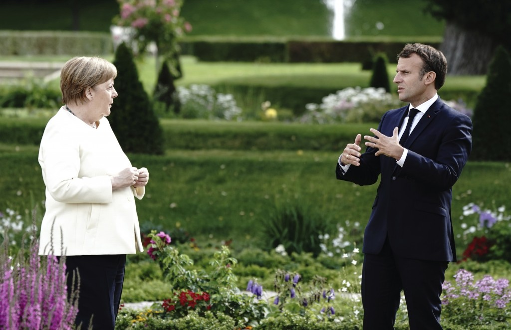 French President Emmanuel Macron gestures as he talks to German Chancellor Angela Merkel during a meeting at Meseberg Castle, the German government's ...